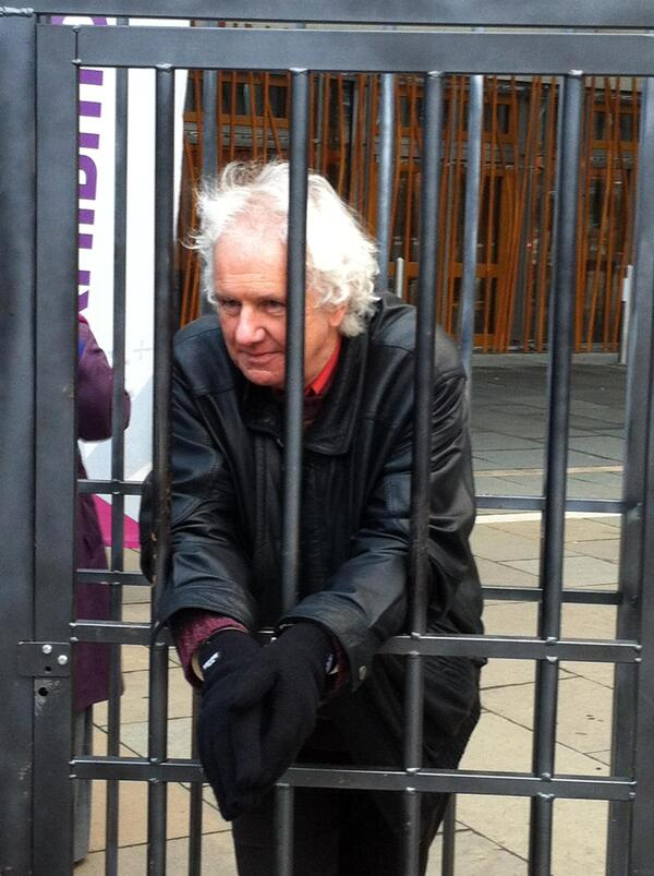 Ron Butlin in cage at Holyrood for PEN inprisoned writers day by Michael MacLeod