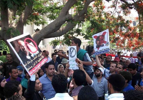 Anti-Shafiq protesters taking cover from the sun under a tree near the Constitutional Court copie
